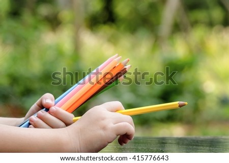 The children's hand holds colour pencils   - stock photo