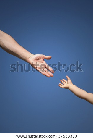 The children's hand reaches for a daddy's hand against the blue  sky - stock photo