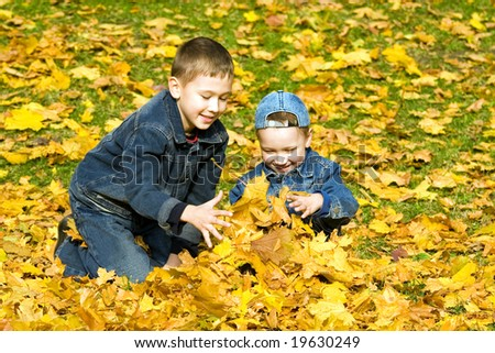 The childs plays with fallen maple leaves - stock photo