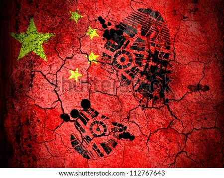 The Chinese flag painted on  cracked ground with vignette with dirty oil footprint over it - stock photo