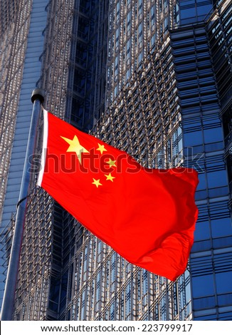 The Chinese flag with a modern building background. - stock photo