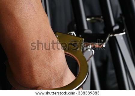 The chrome metal handcuffed bondage on man hand represent the crime and punishment equipment concept related idea. - stock photo