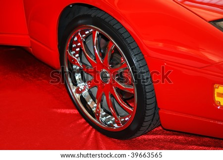 The chromeplated wheel on a red fabric - stock photo