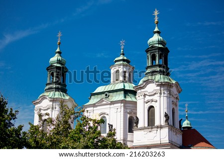 The Church of St. Nicholas behind the trees in Prague, Czech Republic - stock photo