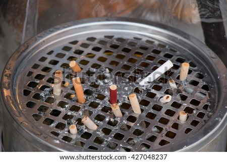 The cigarette stubs in the ashtray. - stock photo