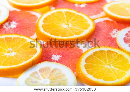 The citrus cut by circles lies on a table. Orange, lemon, grapefruit. Close up, small depth of sharpness - stock photo