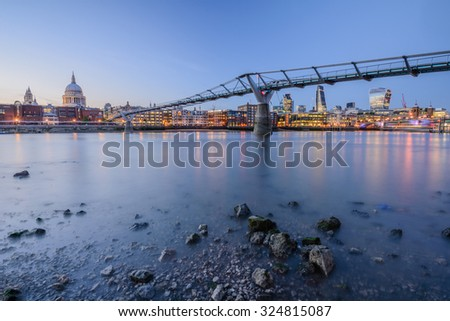 The city of London, St. Paul Cathedral and Millennium bridge over river Thames, long exposure - stock photo