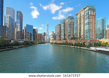 The city skyline along the Chicago River in Chicago, Illinois against a bright blue sky with white clouds - stock photo