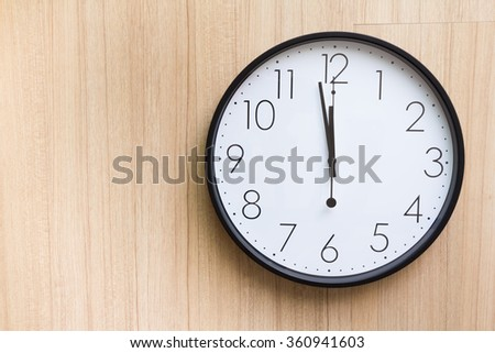 the clock on light wooden wall, show mid-day time with copy space for text on left picture - stock photo