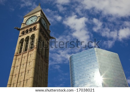 The clock tower - historic Toronto city hall - and the new glass and steel skyscraper with sun reflected in the building surface - stock photo