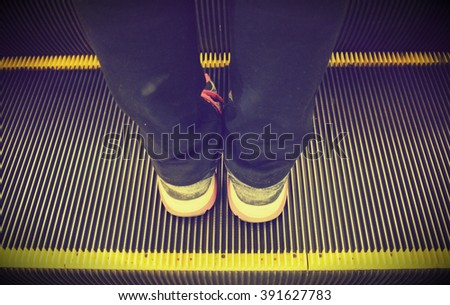 The close up shot of human standing on the escalator processing in low light tone with the black vignette in the corner - stock photo