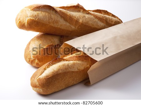 The closeup of french baguette in the paper bag isolated on white. - stock photo