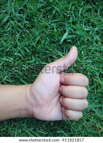 The closeup single hand with Thumb up sign on the green grass background  - stock photo