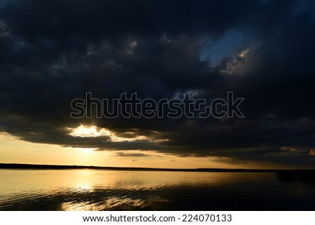The cloud hid the sun over the lake at sunset, the sun's rays broke through the cloud in the sky - stock photo
