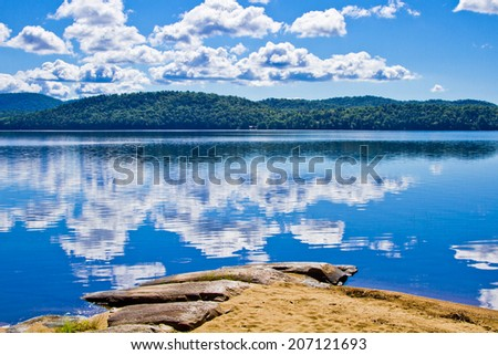 The clouds are reflected in the water of the lake off the beach - stock photo