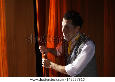 The clown is peeking through  the curtain,before his act - stock photo