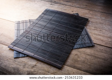 The Coaster, Dark brown bamboo mat on wooden background - stock photo