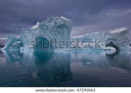 the coastline of east greenland with giant icebergs floating on the sea - stock photo