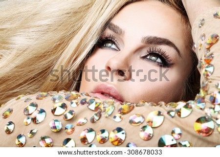 The coat portrait of a beautiful blond woman with green eyes dress with crystals - stock photo