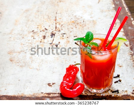 The cocktail bloody mary . Cocktail made of tomatoes, vodka, ice, lime, pepper , salt on rustic background . Free space for text. - stock photo
