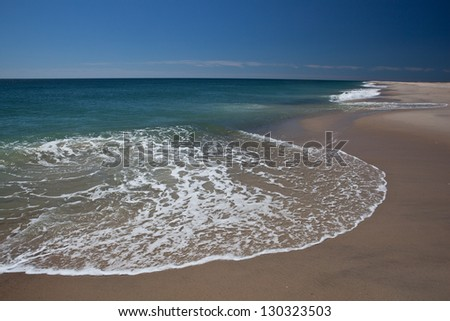 The cold north Atlantic ocean erodes the sand from the Cape Cod National Seashore in Massachusetts.  This sandy peninsula is easily affected by storms and wave action. - stock photo