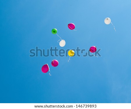 The colorful balloons on the blue sky. Shallow DOF - stock photo