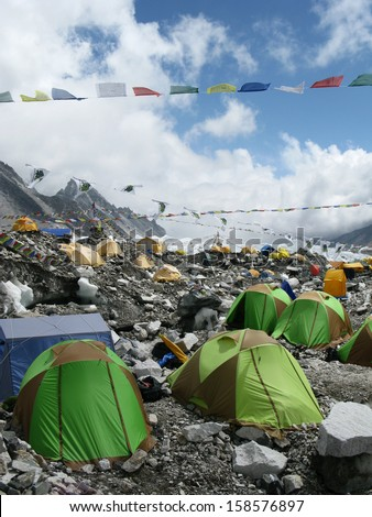 The colorful tents of Everest Base Camp dot the landscape at the foot of Mount Everest in Nepal. - stock photo