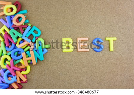 """The colorful word """"BEST"""" next to a pile of other letters over the brown board surface composition. - stock photo"""