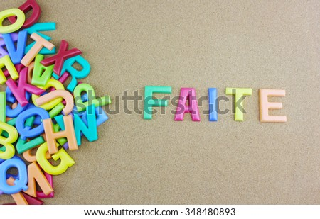 """The colorful word """"FAITE"""" next to a pile of other letters over the brown board surface composition. - stock photo"""