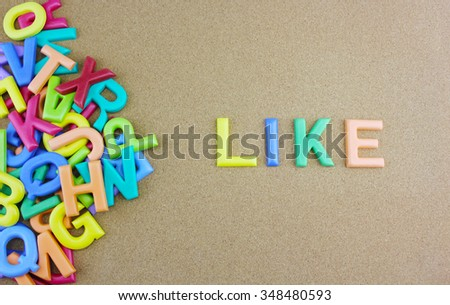 """The colorful word """"LIKE"""" next to a pile of other letters over the brown board surface composition. - stock photo"""