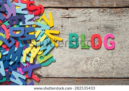 "The colorful words ""BLOG"" made with wooden letters next to a pile of other letters over old wooden board. - stock photo"