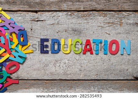 "The colorful words ""EDUCATION"" made with wooden letters next to a pile of other letters over old wooden board. - stock photo"