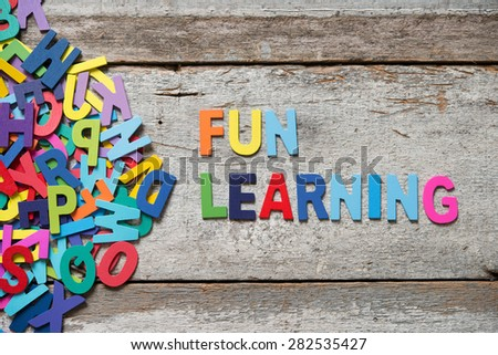 "The colorful words ""FUN LEANRING"" made with wooden letters next to a pile of other letters over old wooden board. - stock photo"