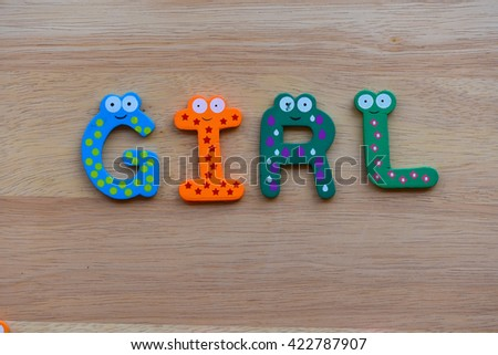 """The colorful words """"Girl"""" made with wooden letters next to a pile of other letters over old wooden board. - stock photo"""