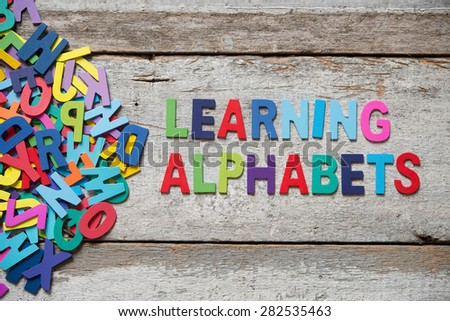 "The colorful words ""LEANRING ALPHABET"" made with wooden letters next to a pile of other letters over old wooden board. - stock photo"