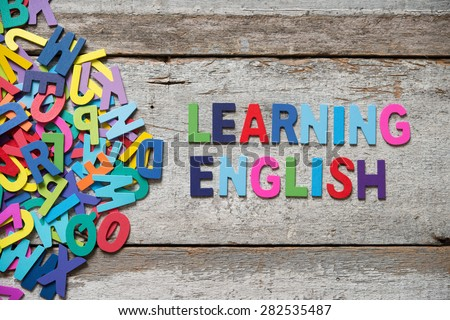 "The colorful words ""LEANRING ENGLISH"" made with wooden letters next to a pile of other letters over old wooden board. - stock photo"