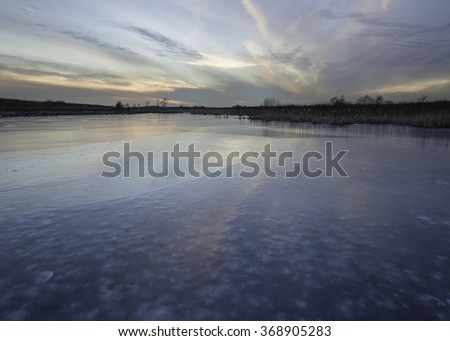 The colors of a winter sunset are reflected in the frozen surface of Crooked Slough.  Springbrook Prairie Nature Preserve, DuPage County, Illinois. - stock photo