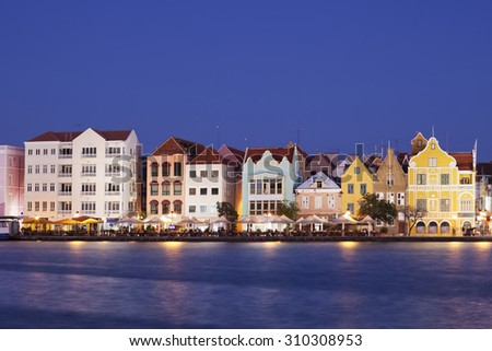 The coloured houses of Willemstad, Curacao in the Netherlands Antilles by night. - stock photo