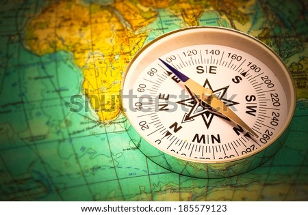 The compass lies on the modern world map - stock photo
