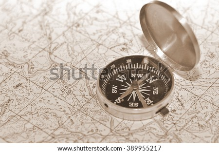 The compass on the map. Magnetic compass is located on a topographic map. - stock photo