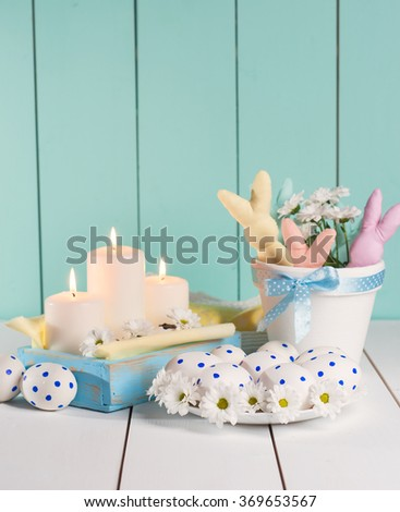 The composition consists of Easter eggs and bunny on colorful wooden background. - stock photo