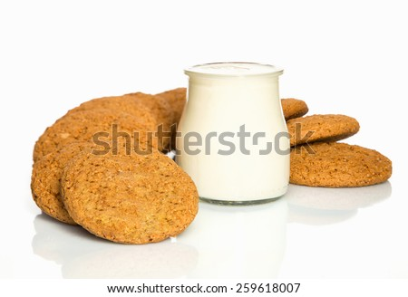 The composition of biscuits and a glass jar with yogurt. Cookies and milk white yogurt, on a white background with reflection. Tasty yellow brown cookies. Yogurt and oatmeal cookies. - stock photo