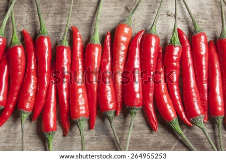 The composition of red hot peppers on a wooden table - stock photo