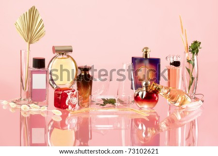 The composition of the various perfume products on a pink background and a true reflection - stock photo