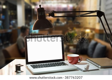 The computer laptop,coffee cup,lamp,notebook,pen is on the work table in office with vintage tone at night time. - stock photo