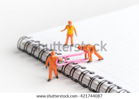 The concept of a collective solution to any problem. Miniature toy workers carry a paper clip. Workers perform disposal of the Chief. Close-up view. - stock photo