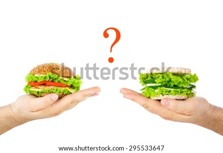 The concept of choosing between harmful junk food and natural health food. A hands holding burger and healthy burger with crispbreads, vegetables, herbs and cheese, between the question mark.  - stock photo