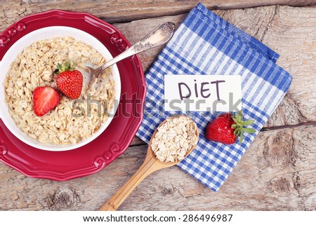 """The concept of dieting, healthy eating, weight loss. Ripe strawberries, oatmeal with milk and a note """"Diet"""". Breakfast in the kitchen. Kitchen table, top view. Morning oatmeal with strawberries. - stock photo"""