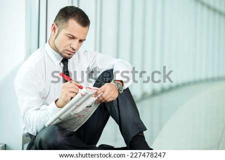 The concept of job search. A man is sitting with a newspaper. - stock photo