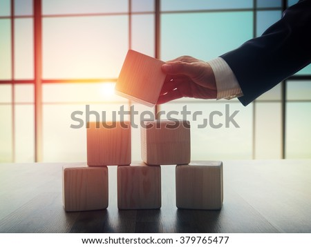 The concept of planning in business. Wooden cubes on a desk in the office. The concept of leadership. Hand men in business suit holding the cubes. - stock photo